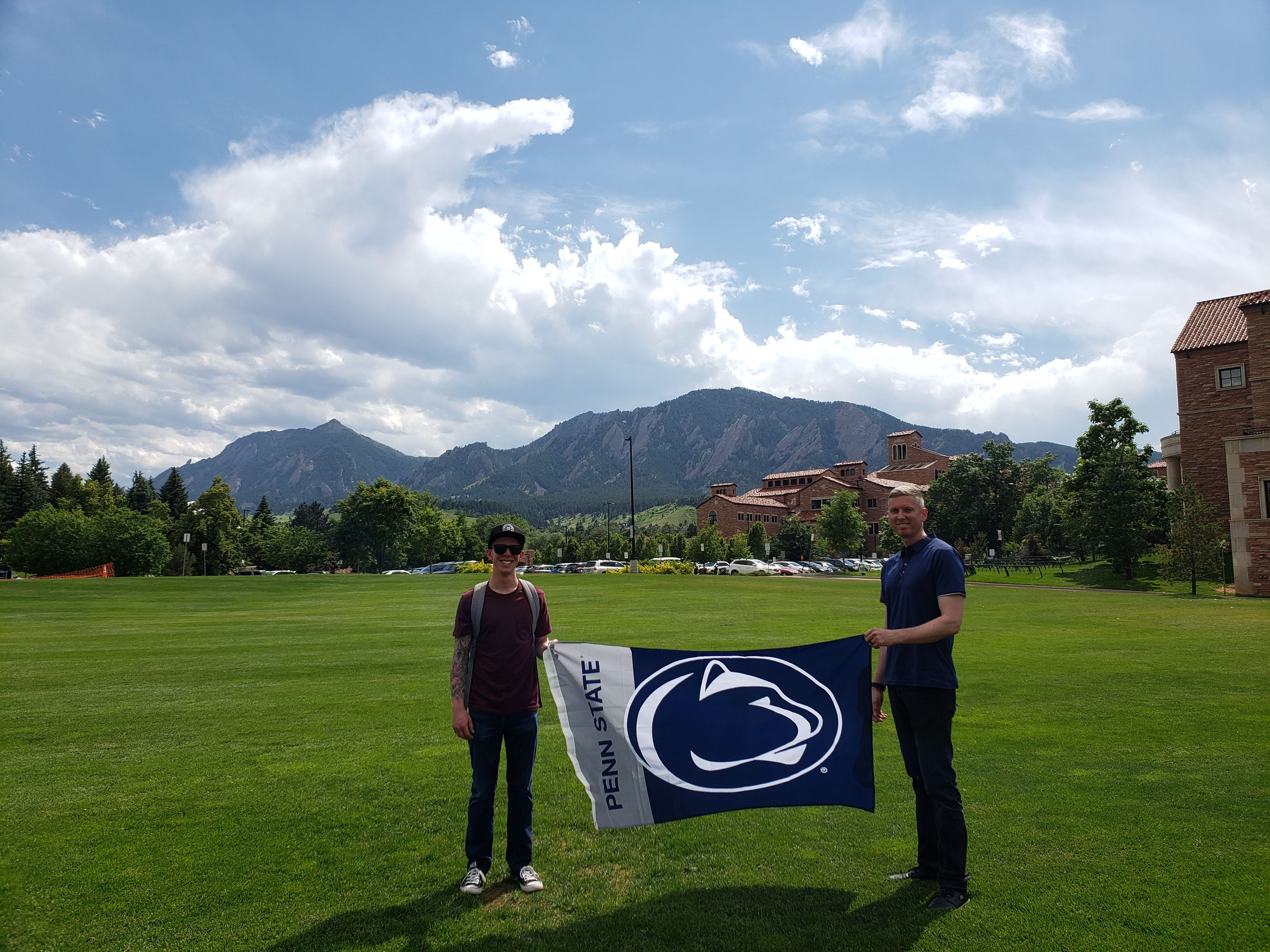 ESP students, Mason Taylor and Joshua Andresky stand on the lawn of the UC Boulder campus holding a PSU flag