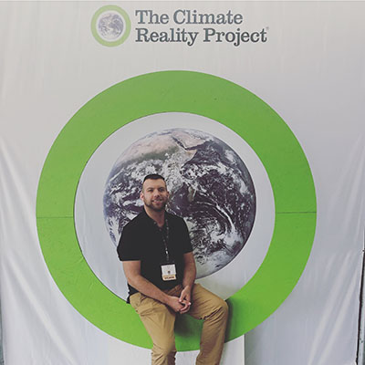 Sean Gray, ESP student sits in front of The Climate Reality Project banner at his recent training experience.